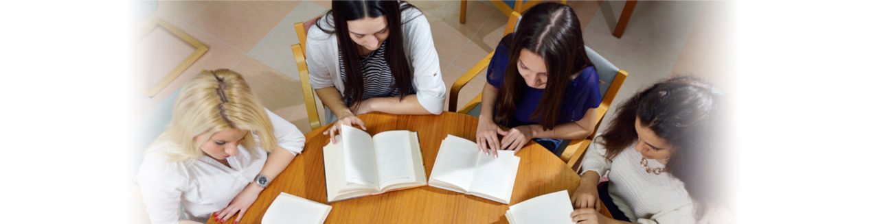 Young girls in a circle reading at a desk